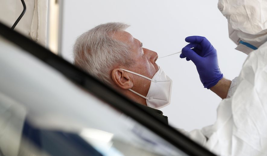 A German help worker tests a French resident working in Germany for COVID-19 at the German-French border near Saarbrucken, Tuesday, March 2, 2021. Germany announced Sunday that travelers from France's northeastern Moselle region will face additional restrictions because of the high rate of variant coronavirus cases there. Travelers from this area must produce a recent negative coronavirus test before entering Germany. The Moselle region in northeastern France includes the city of Metz and borders the German states of Saarland and Rhineland-Palatinate. (AP Photo/Jean-Francois Badias)