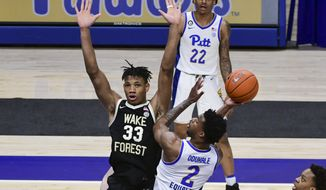 Pittsburgh guard Femi Odukale drives in for a shot against Wake Forest forward Ody Oguama during the first half of an NCAA college basketball game Tuesday, March 2, 2021, in Pittsburgh. (AP Photo/Fred Vuich)