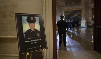 In this Feb. 2, 2021, file photo a placard is displayed with an image of the late U.S. Capitol Police officer Brian Sicknick on it as people wait for an urn with his cremated remains to be carried into the U.S. Capitol to lie in honor in the Capitol Rotunda in Washington. Federal investigators probing the death Sicknick, a U.S. Capitol Police officer killed in the Jan. 6 riot, have zeroed in on a suspect seen on video appearing to spray a chemical substance on the officer before he later collapsed and died, two people familiar with the matter told The Associated Press. (Brendan Smialowski/Pool via AP, File) **FILE**