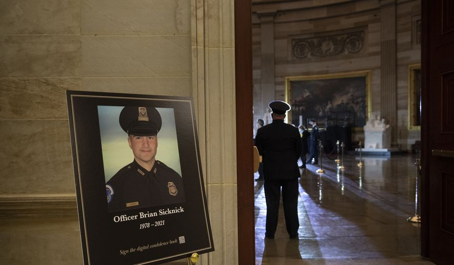 In this Feb. 2, 2021, file photo a placard is displayed with an image of the late U.S. Capitol Police officer Brian Sicknick on it as people wait for an urn with his cremated remains to be carried into the U.S. Capitol to lie in honor in the Capitol Rotunda in Washington. The D.C. medical examiner has yet to release an official cause-of-death termination. (Brendan Smialowski/Pool via AP, File) **FILE**