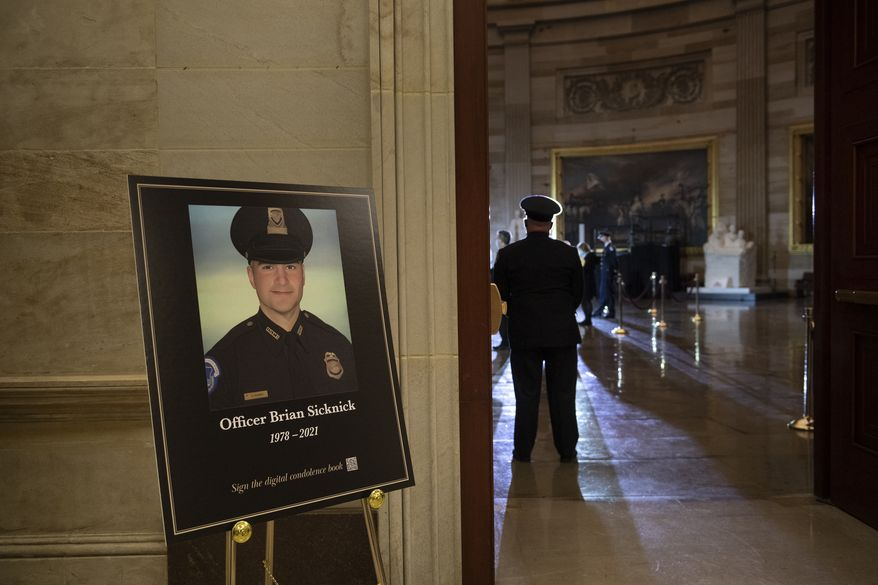 In this Feb. 2, 2021, photo, a placard is displayed with an image of the late U.S. Capitol Police Officer Brian Sicknick on it as people wait for an urn with his cremated remains to be carried into the U.S. Capitol to lie in honor in the Capitol Rotunda in Washington. (Brendan Smialowski/Pool via AP) **FILE**