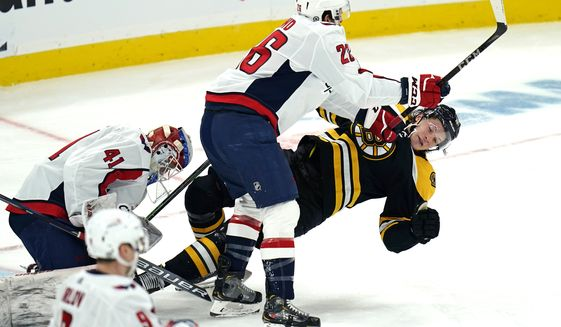 Washington Capitals center Nic Dowd (26) drops Boston Bruins center Trent Frederic, right, to the ice on a hard check during the second period of an NHL hockey game, Wednesday, March 3, 2021, in Boston. (AP Photo/Charles Krupa)