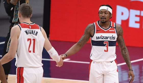 Washington Wizards guard Bradley Beal (3) and center Moritz Wagner (21) react during the first half of an NBA basketball game against the Memphis Grizzlies, Tuesday, March 2, 2021, in Washington. (AP Photo/Nick Wass)