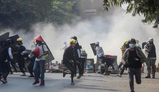 Anti-coup protesters run from tear gas and charging riot police and soldiers in Mandalay, Myanmar, Wednesday, March 3, 2021. Demonstrators in Myanmar took to the streets again on Wednesday to protest last month's seizure of power by the military. (AP Photo)