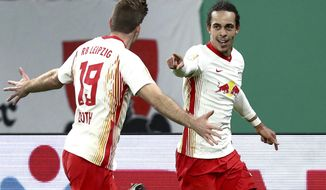 Leipzig's scorer Yussuf Poulsen, right, and his teammate Alexander Sorloth, left, celebrate the opening goal during the German soccer cup, DFB Pokal, quarter final match between RB Leipzig and VfL Wolfsburg in Leipzig, Germany, Wednesday, March 3, 2021. (AP Photo/Michael Sohn)