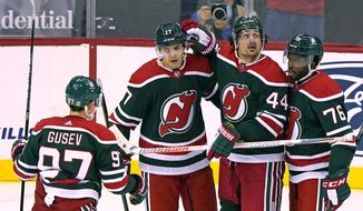 New Jersey Devils left wing Nikita Gusev (97), center Yegor Sharangovich (17) and defenseman P.K. Subban (76) celebrate with left wing Miles Wood (44) after Wood scored during the third period of the team's NHL hockey game against the New York Islanders, Tuesday, March 2, 2021, in Newark, N.J. (AP Photo/Kathy Willens)