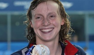 This July 27, 2019, file photo shows gold medalist United States' Katie Ledecky posing with her medal following the women's 800m freestyle final at the World Swimming Championships in Gwangju, South Korea. Ledecky is a native of Bethesda, Md., a suburb of Washington, D.C. and among at least 40 D.C.-area swimmers are taking part in the Tokyo Olympics swimming trials, hopeful to go for the gold as part of Team USA. (AP Photo/Lee Jin-man, File) **FILE**