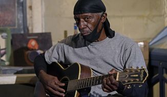 """Bluesman Jimmy """"Duck"""" Holmes plays a quick ditty at the Blue Front Cafe in Bentonia, Miss., Jan. 21, 2021. Holmes' ninth album, """"Cypress Grove,"""" has earned a Grammy nomination for the Best Traditional Blues Album. (AP Photo/Rogelio V. Solis)"""