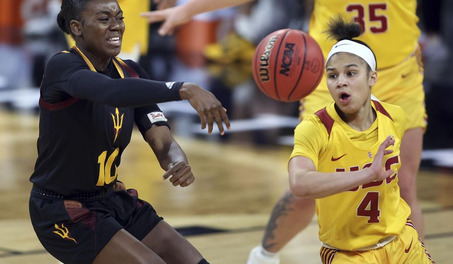 Arizona State guard Iris Mbulito (10) passes as Southern California guard Endyia Rogers (4) defends during an NCAA college basketball game in the first round of the Pac-12 women's tournament Wednesday, March 3, 2021, in Las Vegas. (AP Photo/Isaac Brekken)