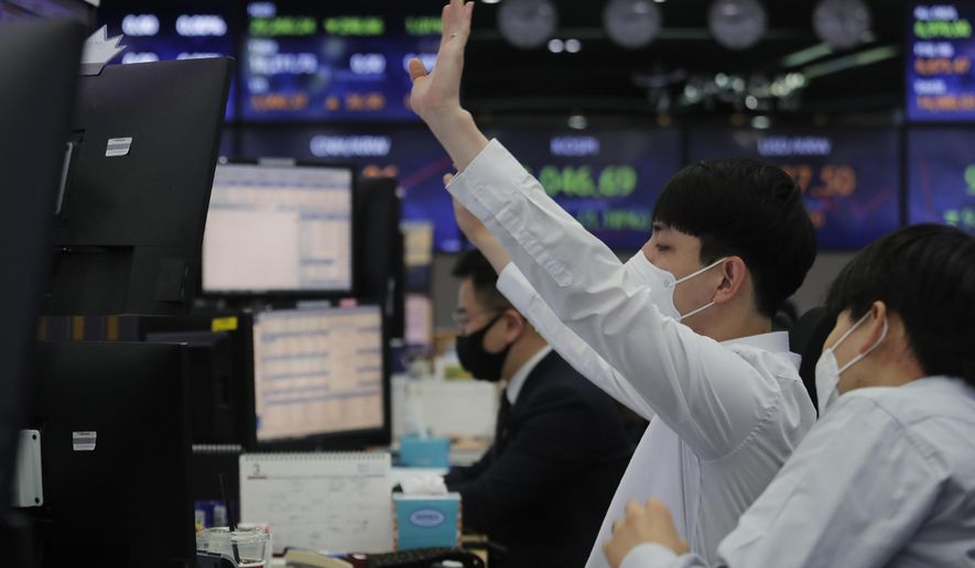 A currency trader gestures at the foreign exchange dealing room of the KEB Hana Bank headquarters in Seoul, South Korea, Thursday, March 4, 2021. Asian shares fell Thursday, tracking a decline on Wall Street as another rise in bond yields rattled investors who worry that higher inflation may prompt central banks to raise ultra-low interest rates. (AP Photo/Ahn Young-joon)