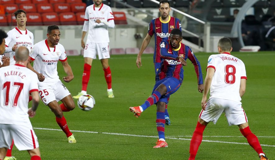Barcelona's Ousmane Dembele, 2nd right, attempts a shot at goal during the the Copa del Rey semifinal, second leg, soccer match between FC Barcelona and Sevilla FC at the Camp Nou stadium in Barcelona, Spain, Wednesday March 3, 2021. (AP Photo/Joan Monfort)