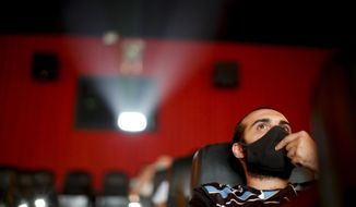 A man watches a movie at a cinema after almost a year of theaters being closed due to the COVID-19 pandemic, in Buenos Aires, Argentina, Wednesday, March 3, 2021. (AP Photo/Natacha Pisarenko)