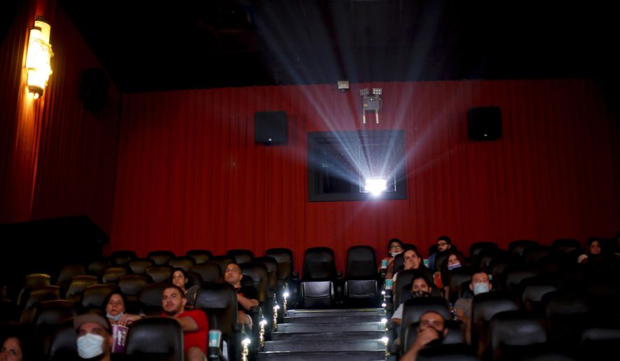 People watch a movie at a cinema after almost a year of theaters being closed due to the COVID-19 pandemic, in Buenos Aires, Argentina, Wednesday, March 3, 2021. (AP Photo/Natacha Pisarenko)