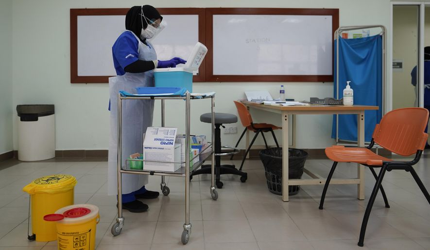 A health worker prepares to administer the Pfizer's COVID-19 vaccine to a health staff member at the Hospital UiTM in Sungai Buloh, outskirts of Kuala Lumpur, Malaysia, Wednesday, March 3, 2021. (AP Photo/Vincent Thian)