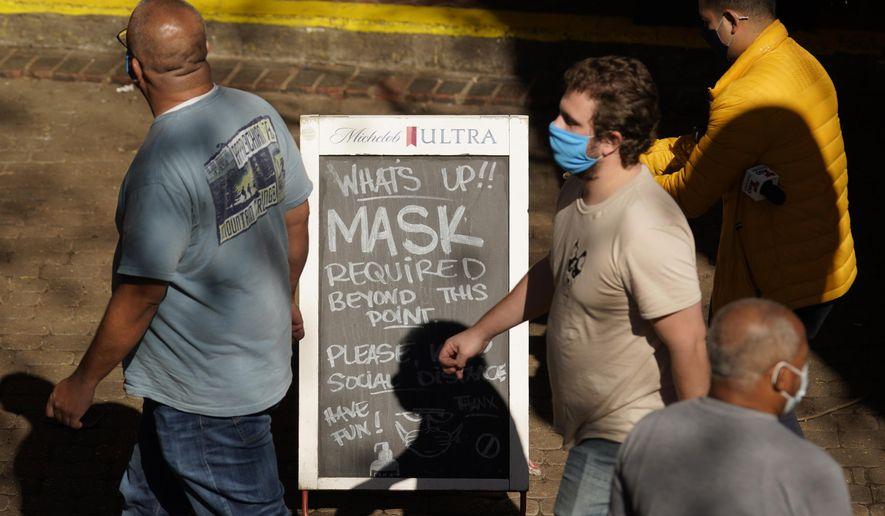 Visitors wearing face masks walk past a sign requiring masks at a restaurant along the River Walk, Wednesday, March 3, 2021, in San Antonio. Gov. Greg Abbott says Texas is lifting a mask mandate and lifting business capacity limits next week. (AP Photo/Eric Gay) **FILE**