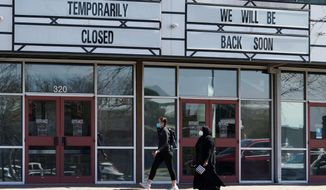 Shoppers pass a theater closed due to the COVID-19 outbreak, Wednesday, March 3, 2021, in San Antonio, Texas. (AP Photo/Eric Gay)  **FILE**