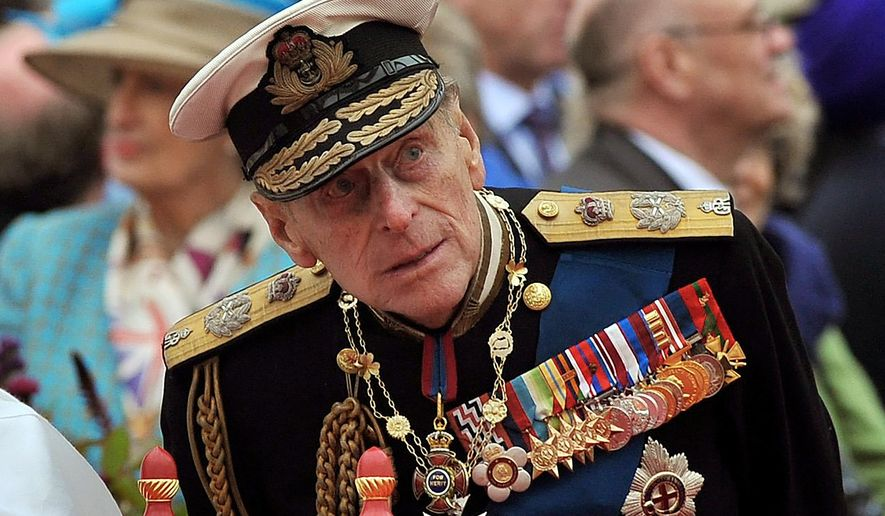 """A Sunday June 3, 2012, photo from files showing Prince Philip watching the proceedings from the royal barge during the Diamond Jubilee Pageant on the River Thames in London. Buckingham Palace said Thursday March 4, 2021, that Prince Philip has undergone a successful procedure for a pre-existing heart condition, and will remain in hospital """"for a number of days."""" (AP Photo/John Stillwell, Pool File)"""