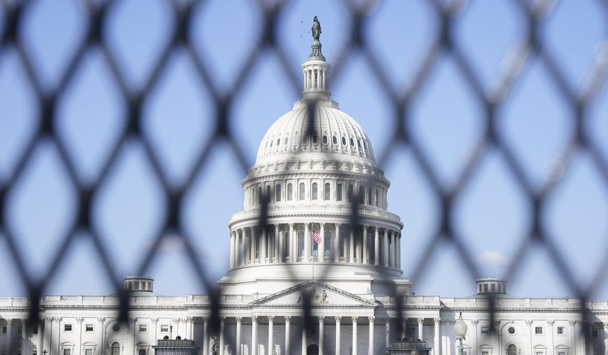 The Capitol is seen through security fencing, Thursday, March 4, 2021, on Capitol Hill in Washington. (AP Photo/Jacquelyn Martin)