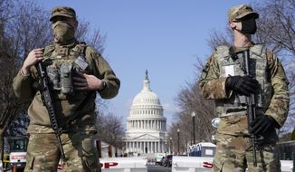 In this file photo, National Guard troops keep watch on the Capitol, Thursday, March 4, 2021, on Capitol Hill in Washington. (AP Photo/Jacquelyn Martin) ** FILE **
