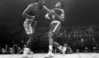 FILE - Joe Frazier hits Muhammad Ali with a left during the 15th round of their heavyweight title fight at New York's Madison Square Garden, in this March 8, 1971, file photo. Frazier was a relentless puncher filled with rage toward a fighter who couldnt help but belittle him.(AP Photo/File)