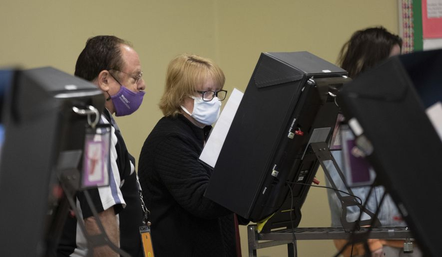 A technician watches as a poll worker tries to use a voting machine after experiencing issues in Georgia's Senate runoff elections at a senior center, Tuesday, Jan. 5, 2021, in Acworth, Ga. (AP Photo/Branden Camp) ** FILE **