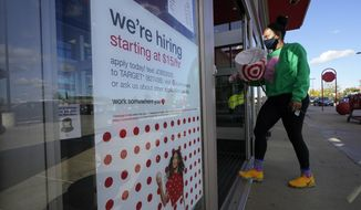 In this Sept. 30, 2020, photo, a passerby walks past a hiring sign while entering a Target store in Westwood, Mass. (AP Photo/Steven Senne) **FILE**