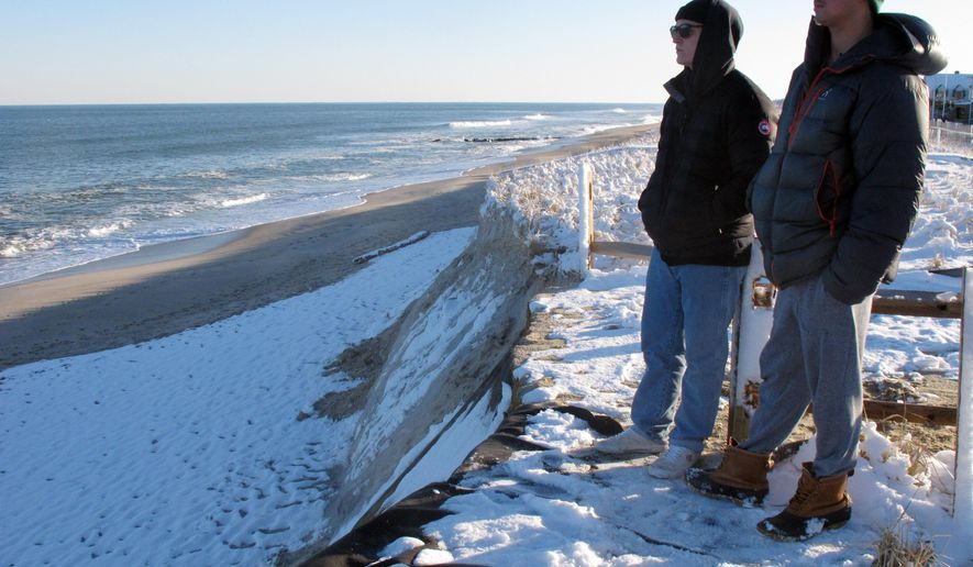 FILE - In this Feb. 8, 2021, file photo, spectators look out over a severely eroded beach on Bay Head, N.J. New Jersey is considering doubling its budget for beach restoration projects, to $50 million a year. (AP Photo/Wayne Parry, File)