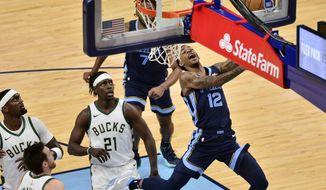 Memphis Grizzlies guard Ja Morant (12) shoots ahead of Milwaukee Bucks guard Jrue Holiday (21) in the second half of an NBA basketball game Thursday, March 4, 2021, in Memphis, Tenn. (AP Photo/Brandon Dill)