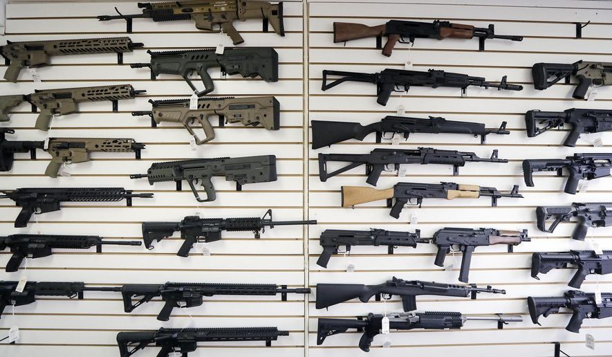 In this Oct. 2, 2018, file photo, semi-automatic rifles fill a wall at a gun shop in Lynnwood, Wash. With Democrats controlling the presidency and Congress, Republican state lawmakers concerned about the possibility of new federal gun control laws aren't waiting to react. Legislation in at least a dozen states seeks to nullify any new restrictions, such as ammunition limits or a ban on certain types of weapons. (AP Photo/Elaine Thompson, File)