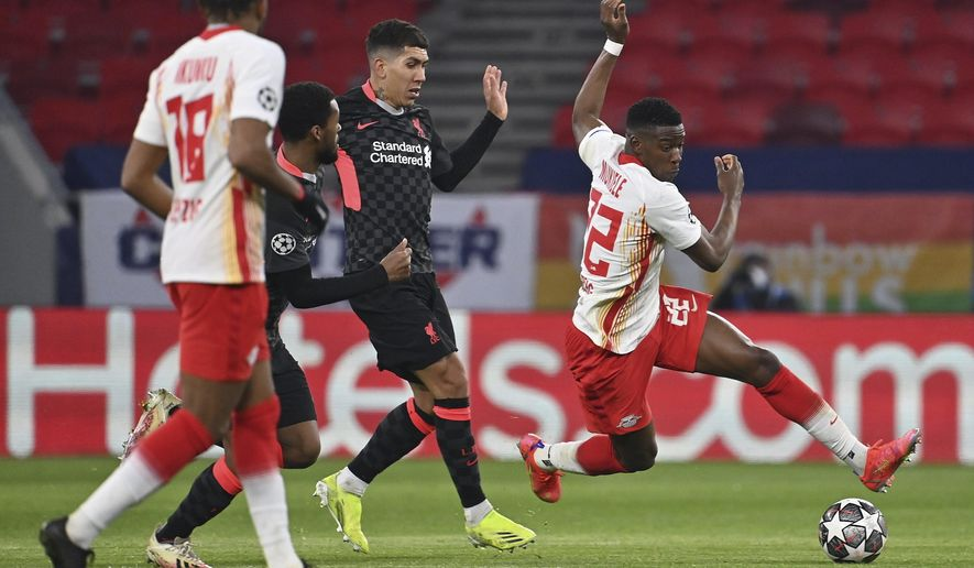 RB Leipzig's Nordi Mukiele, right, tries to get past Liverpool's Roberto Firmino, center, during the Champions League round of 16, first leg, soccer match between RB Leipzig and Liverpool in the Puskas Ferenc Arena in Budapest, Hungary, Tuesday, Feb. 16, 2021. At right Lukas Klostermann of RB Leipzig. (Tibor Illyes/MTI via AP)