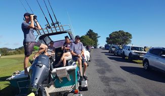 John Fitzgerald, left, on holidays with his wife Rita and friends, scans the horizon from high ground for any sign of a tsunami near Waitangi, New Zealand, Friday, March 5, 2021. A powerful magnitude 8.1 earthquake struck in the ocean off the coast of New Zealand prompting thousands of people to evacuate and triggering tsunami warnings across the South Pacific. (Peter De Graaf/New Zealand Herald via AP)