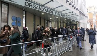 FILE - In this file photo dated Friday, March 6, 2020, before the coronavirus pandemic restrictions, people stand outside the headquarters of the Organization of the Petroleum Exporting Countries, OPEC, in Vienna, Austria.  Members of oil producer cartel OPEC and allied countries are meeting online Thursday March 4, 2021,  considering a possible increase in production now that prices have recovered to near their pre-pandemic levels.  (AP Photo/Ronald Zak, FILE)