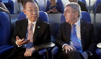 FILE - In this Aug. 5, 2016, file photo, then U.N. Secretary-General Ban Ki-moon, left, talks with International Olympic Committee President Thomas Bach in Maracana Stadium before the opening ceremony for the 2016 Summer Olympics in Rio de Janeiro, Brazil. Ban is being asked to rule on an ethics complaint filed against the International Olympic Committee by a human-rights group representing Uyghurs and other ethnic minorities in China. (AP Photo/Mark Humphrey, Pool)