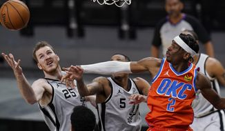 Oklahoma City Thunder guard Shai Gilgeous-Alexander (2) battles San Antonio Spurs center Jakob Poeltl (25) and guard Dejounte Murray (5) for a rebound during the second half of an NBA basketball game in San Antonio, Thursday, March 4, 2021. (AP Photo/Eric Gay)