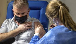 A healthcare worker administers a dose of the AstraZeneca COVID-19 vaccine to a Brussels police chief inspector Didier Bruer at the Brussels Expo center in Brussels, Thursday, March 4, 2021. The Expo is one of the largest vaccination centers in Belgium. (AP Photo/Olivier Matthys)