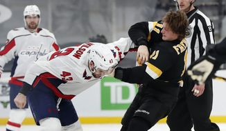 Boston Bruins' Trent Frederic (11) and Washington Capitals' Tom Wilson (43) fight during the third period of an NHL hockey game, Friday, March 5, 2021, in Boston. (AP Photo/Michael Dwyer)