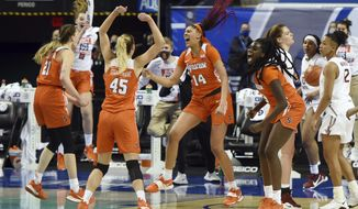 Syracuse players mob Kamilla Cardoso (14) after she hit the game-winning shot at the buzzer to beat Florida State =in an NCAA college basketball game in the quarterfinals of the Atlantic Coast Conference tournament, Friday, March 5, 2021, at the Greensboro Coliseum in Greensboro, N.C. (Walt Unks/The Winston-Salem Journal via AP, Pool)