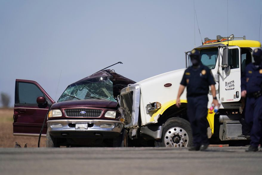 In this Tuesday, March 2, 2021, file photo, law enforcement officers work at the scene of a deadly crash in Holtville, Calif. Nine migrants in an SUV packed with 25 people that drove through an opening in a border wall suffered major injuries after their vehicle slammed into a tractor-trailer and killed 13 others inside, the California Highway Patrol said Thursday, March 4, 2021. (AP Photo/Gregory Bull, File)