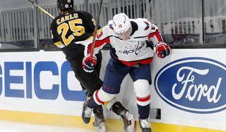 Boston Bruins' Brandon Carlo (25) checks Washington Capitals' Jakub Vrana (13) during the first period of an NHL hockey game Friday, March 5, 2021, in Boston. (AP Photo/Michael Dwyer)