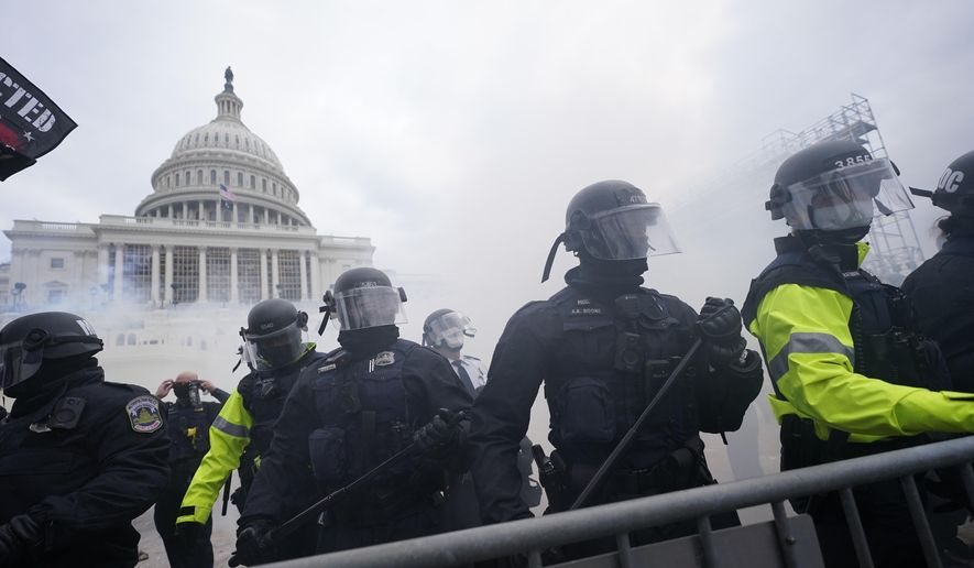 In this Jan. 6, 2021, file photo, police stand guard after holding off rioters who tried to break through a police barrier at the Capitol in Washington. (AP Photo/Julio Cortez, File)