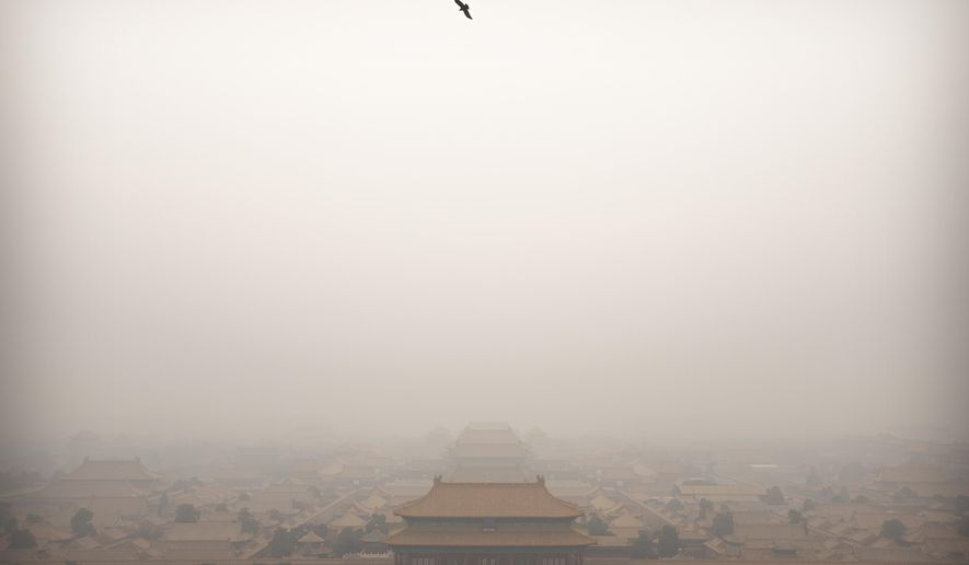 FILE - In this Jan. 18, 2020, file photo, a bird flies over the Forbidden City on a day with high levels of air pollution in Beijing. China's Premier Li Keqiang announced that the country would target a reduction of 18% in carbon intensity over the course of the next five years as part of the meeting of the ceremonial legislature which kicked off its annual meeting Friday, March 5, 2021. (AP Photo/Mark Schiefelbein, File)