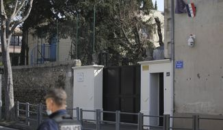 A police officer guards a Jewish school after a man visibly brandished a knife outside a Jewish school and a kosher market in Marseille, southern France, Friday, March 5, 2021. Police detained a man Friday who was wielding a knife outside a Jewish school and kosher market, and increased surveillance of Jewish sites in the city while they investigate his motives, according to local authorities. (AP Photo/Daniel Cole)