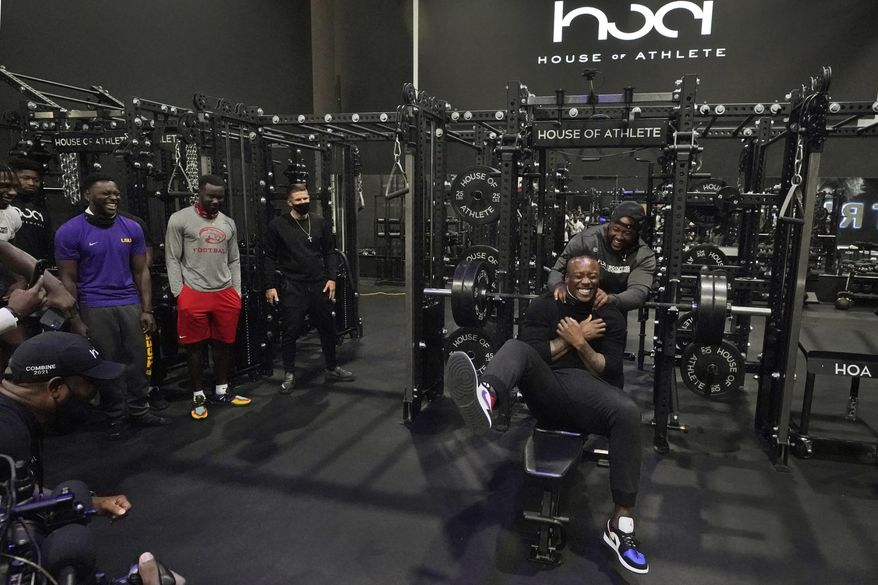 House of Athlete Scouting Combine founder and former NFL player Brandon Marshall, right foreground, is congratulated by Isaiah Ross after Marshall completed a series of bench presses for the combine participants on the second day of the House of Athlete Scouting Combine, Thursday, March 4, 2021, in Weston, Fla. (AP Photo/Wilfredo Lee)