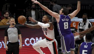 Portland Trail Blazers guard Damian Lillard, left, dives to the basket as Sacramento Kings forward Nemanja Bjelica defends during the first half of an NBA basketball game in Portland, Ore., Thursday, March 4, 2021. (AP Photo/Steve Dykes)