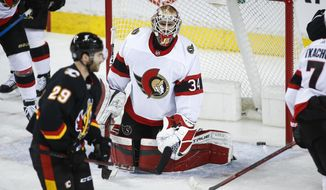 Ottawa Senators goalie Joey Daccord, right, reacts to letting in a goal as Calgary Flames' Dillon Dube looks on during the second period of an NHL hockey game, Thursday, March 4, 2021 in Calgary, Alberta. (Jeff McIntosh/The Canadian Press via AP)