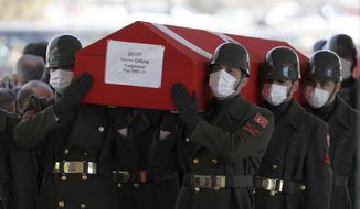 Soldiers carry the coffin of army general Osman Erbas as Turkish leaders, army commanders, family members and olleagues attend funeral prayers and a ceremony for 11 military personnel, including a high-ranking officer, at Ahmet Hamdi Akseki Mosque, in Ankara, Turkey, Friday, March 5, 2021. Turkish army officers were killed on Thursday when an army helicopter crashed in a snow-covered mountainous area in Bitlis, eastern Turkey. (AP Photo/Burhan Ozbilici)