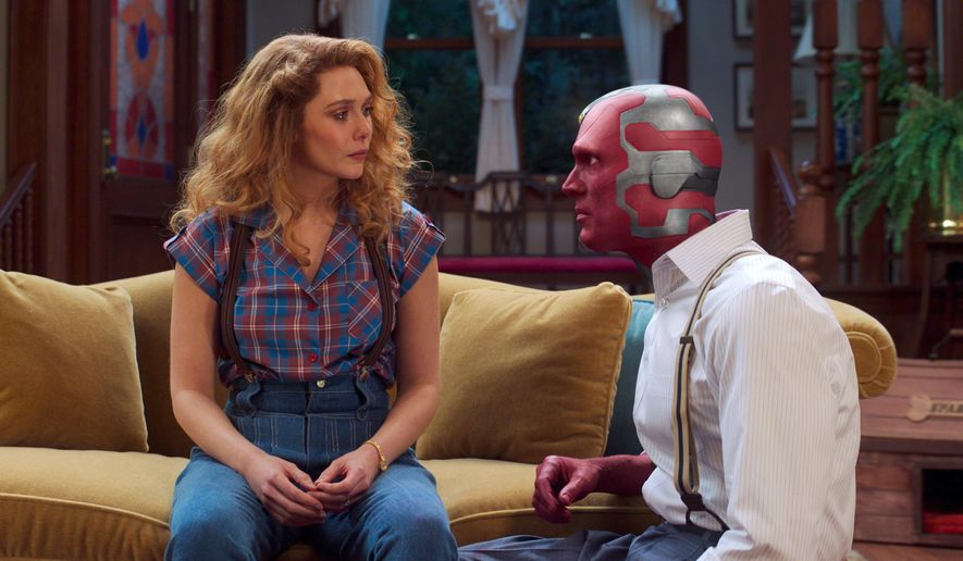 """This image released by Disney+ shows Elizabeth Olsen, left and Paul Bettany in a scene from """"WandaVision."""" (Disney+ via AP)"""