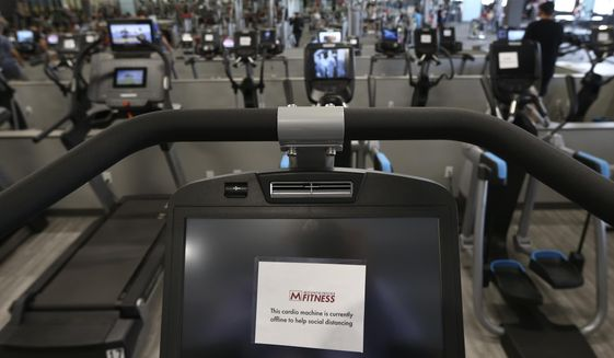 This July 2, 2020, file photo shows some gym equipment machines are turned off so clients can physically distance at Mountainside Fitness in Phoenix. (AP Photo/Ross D. Franklin, File)