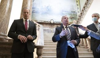 Senate Minority Whip John Thune, R-S.D., left, and Sen. Lindsey Graham, R-S.C., pause outside the Senate chamber to talk with reporters during a delay in work on the Democrats' $1.9 trillion COVID-19 relief bill, at the Capitol in Washington, Friday, March 5, 2021. (AP Photo/J. Scott Applewhite)