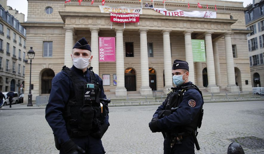 Police officers stand outside the occupied iconic Odeon theater, Friday, March 5, 2021 in Paris. Out-of-work French culture and tourism workers have occupied the theater on Paris' Left Bank to demand more government support after a year of pandemic that has devastated their livelihoods. (AP Photo/Francois Mori)